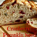 Loaf of Cranberry Pumpkin Seed Artisan Yeast Bread sliced on a wooden cutting board.