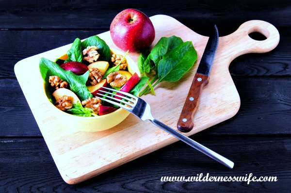 Cutting board with apple, spinach leaves, knife, fork and cream colored bowl full of apple spinach salad.