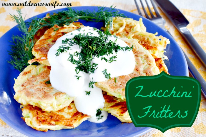 A blue plate loaded with delicious golden brown zucchini fritters drenched in yummy sour cream dill sauce.