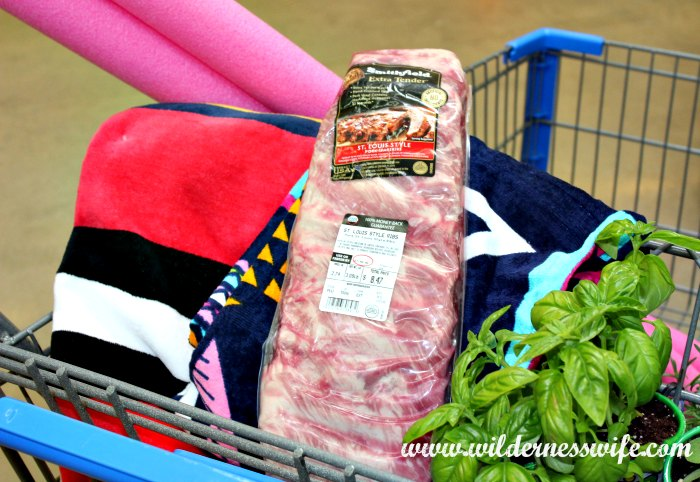 Walmart shopping cart loaded with items for pool party including package of Smithfield Extra Tender Pork Back Ribs.