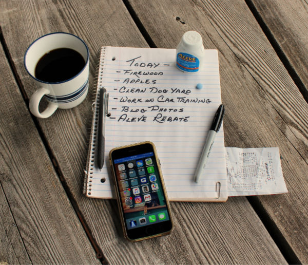 Planning a busy day with a cup of coffee, notepad, smartphone, list, and bottle of Aleve - my goto pain relief.