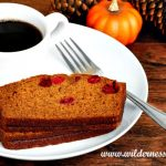 Pumpkin cranberry bread on a white plate with a cup of coffee and a mini pumpkin