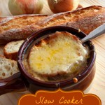 A bowl of steaming Slow Cooker French Onion Soup with a slice of crusty french bread and melted cheese on top.