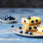 Stack of No-Bake Blueberry Cheesecake Bars on a grey plate sprinkled with lemon zest