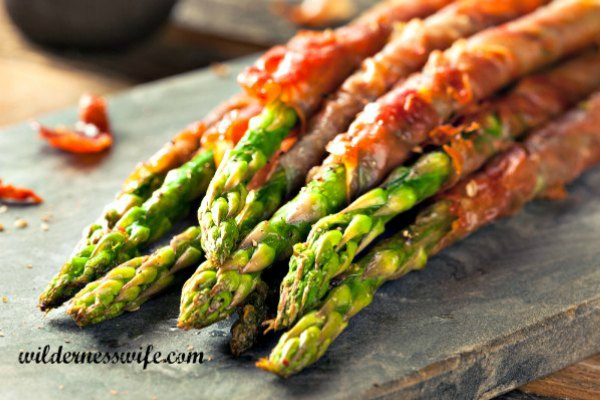 Our Bacon Wrapped Asparagus Recipe on a cutting board showing roasted asparagus spears wrapped in crispy bacon.