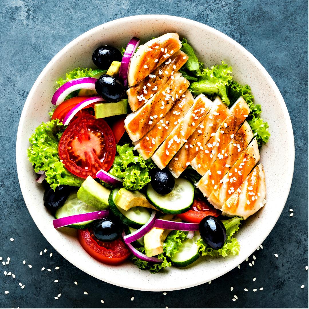 Marinated grilled chicken breaston a summer green salad