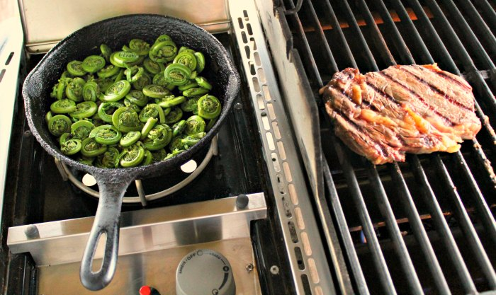 Sauteed fiddleheads cooking in cast iron skillet on gas grill side burner next to seared rib eye steak