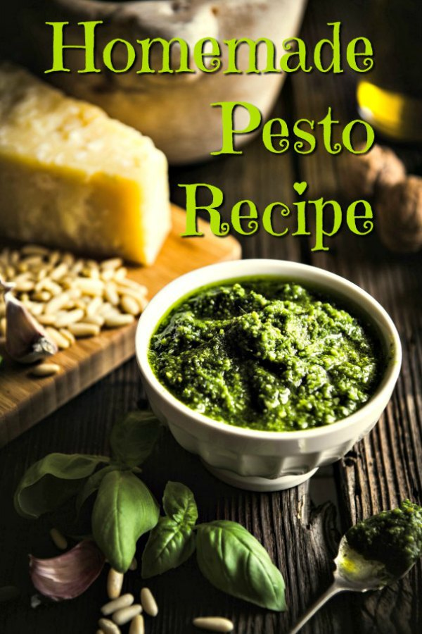 Homemade basil pesto in a cream bowl sitting on a dark wooden table. Parmesan cheese, pine nuts, garlic cloves and basil leaves are scattered around the bowl.