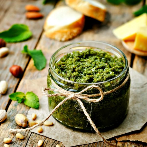 Jar of green pesto sitting on a wooden table with pine nuts, pistachios, basil leaves, and Parmesan cheese nearby.