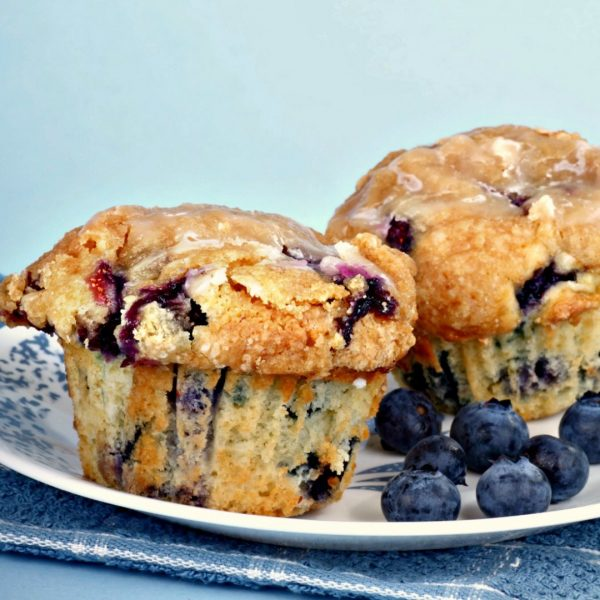 2 muffins made with the Jordan Marsh Blueberry Muffin Recipe  sitting on blue and white plate