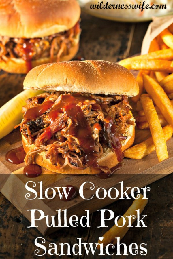 Juicy slow cooker pulled pork sandwich sitting on wooden cutting board with a side of french fries
